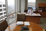 A First Financial employee works at his desk with a view of downtown Cincinnati outside his windows.