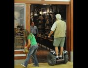 """""""Jungle"""" Jim Bonaminio, using his Segway, stops in to check on Colonel De, who is opening up his second location at Jungle Jim's."""