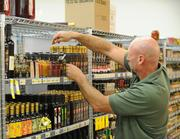 Wayne Scibert, international manager, arranges the bottles in the balsamic vinegar area.
