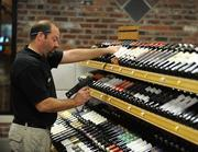 Rob Jeffries, liquor store manager, works on the massive wine display.