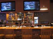 A view of the full bar and its flat-screen TVs.
