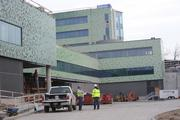 The hospital's exterior tile fades to a light green at the loading dock area.