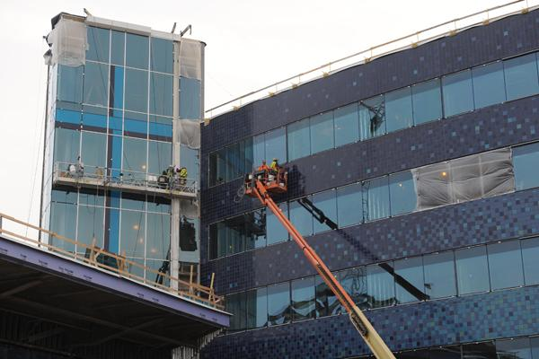 Workers are finishing up construction on the glass exterior. Here you can see one of two crosses that are incorporated into the design of the hospital.
