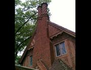 "A tall exterior chimney divides into two twisting ""chimney pots"" of brick."