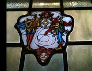 Diamond and square-pane leaded windows are arranged in singles, pairs and other groupings. This one has images of jesters.