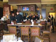 Employees prepare for guests at the bar located inside Ruth's Chris Steak House.