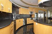 The kitchen has top-of-the-line appliances and black granite floors and counters.