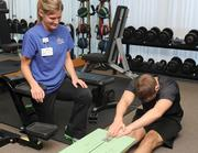 A TriHealth employee stretches out with a fitness consultant watching.