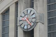 The face of the historic building's clock has panels of glass that are cracked.