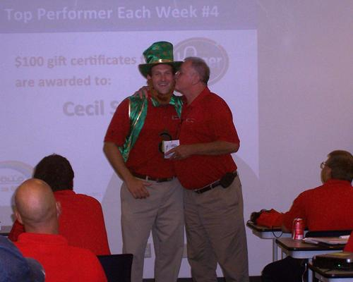 Apollo Heating, Cooling and Plumbing CEO Jamie Gerdsen, dressed as a leprechaun, gets a kiss from one of his employees.