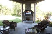 The outdoor space of the Dennison has a TV mounted above a wood-burning fireplace.