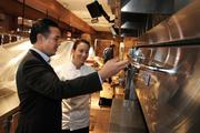 A brick oven in the open kitchen at Seasons 52. Jong is standing with Angela Delmark, one of the restaurant's sous chefs.