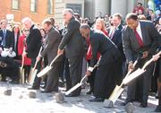 From left to right: John Schneider, Peter Rogoff, administrator of the FTA, LaHood, Mallory and Dohoney use gold shovels to turn cobblestones on Elm Street.