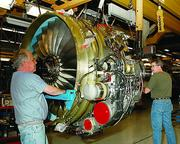 Geoffrey Wallace and Keith Langevin, production mechanics at GE's Evendale plant align the low-pressure turbine with the engine core during assembly of  a CFM56-7 engine.