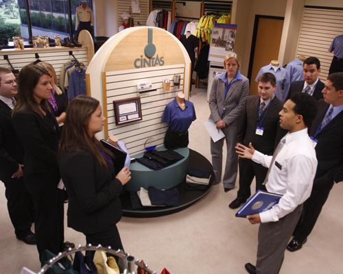 About 30 UC students took part in a sales symposium at Cintas headquarters. Guide Alex Schutte leads a small group on a tour.