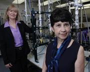 "Melinda Kruyer, left, Confluence's executive director, and Sally Gutierrez of the U.S. EPA, stand in the EPA's lab near the University of Cincinnati in Clifton. Confluence is working to harness the region's powerful water ""assets"" to grow the local economy."