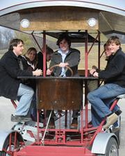 Pedal Wagon passengers face each other while helping to propel the vehicle.