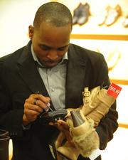 Employee Michael Graham uses a handheld device to check inventory at Macy's in Kenwood.