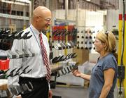 Lucinda Humphrey talks with Metalworking Group President Mike Schmitt with newly painted metal parts hanging to dry.