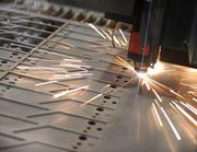 A laser cutter is used to cut out metal parts for fitness equipment at Metalworking Group in Colerain Township.