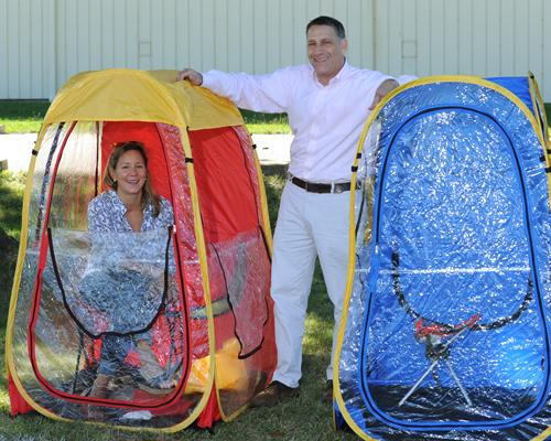 Under-the-Weather co-founder Rick Pescovitz and his wife and co-founder, Kelly Mahan, demonstrate the tent Pescovitz designed on a soccer field in Blue Ash.
