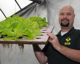 Urban Harvest founder Brad Rogers displays produce grown via a method that combines fish and vegetable farming. The company will target local restaurants and families for its products.