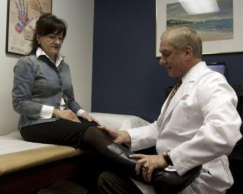 Dr. Robert Heidt Jr., the new CEO of Wellington Orthopaedic & Sports Medicine, helps a patient.
