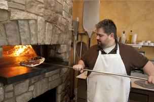 Will DeLuca, owner of Betta's Italian Oven on Montgomery Road in Norwood, bakes wood-fired pizzas during the lunch rush. The restaurant's annex, Café Cornetti, is preparing to open.