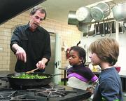Waldorf teacher Peter Tomshany cooks a meal with Indira Thompson and Phoenix Haigis.