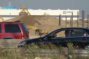 Cars pass very close to the construction but most of the work is hidden within the lower area of the site.