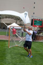 An Ohio Machine player attempts to catch a lacrosse ball near a goal set up for the game.