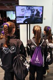 A trio of young gymnasts at the Arnold Sports Festival watch one of the day's events on a monitor.