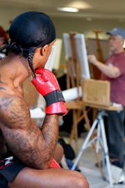 A model poses for a group of artists who are drawing him at the Arnold Sports Festival.