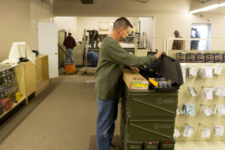Co-owner Eric Delbert prepares to add to LEPD Firearms & Range's inventory days before the facility opened.