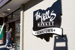 Workers are outfitting the Hills Market in downtown Columbus' Discovery District with shelves as the grocery heads toward a March opening.