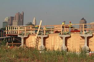 A new bridge on I-670 west over Cleveland Avenue takes shape the with the downtown skyline in the backgound.