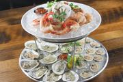 The Shellfish Tower offers a dozen oysters and clams on the half shell, a half pound of peel and eat gulf shrimp and crab with cocktail sauce and horseradish mignonette.