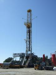 A drilling rig stands about 100 feet above a well pad under development in the Utica shale play near Marietta.