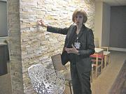 "Janet Meeks, St. Ann's president, explains the project in the ""vision room"" with samples of stone wall finishes to go the addition and chairs for staff to test out before buying them."