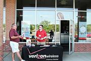 John Betts, manager of a Verizon wireless store without power in Pickerington, set up out front to give customers information on phone plans, even if he wasn't able to sell any. Whitehall resident Dan Espinoza is also without power.