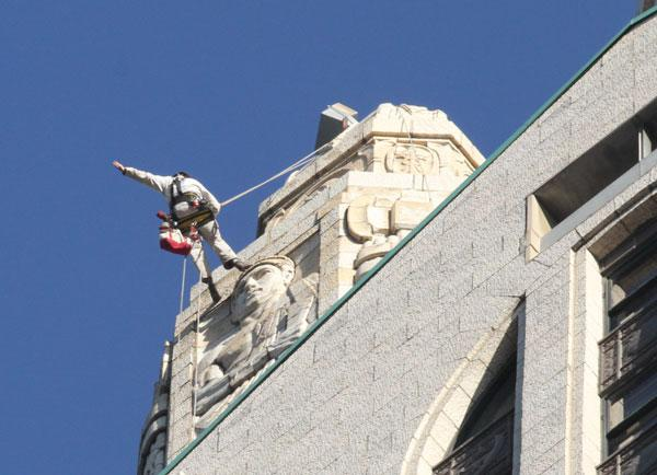 Kelly Streeter with Vertical Access rappels down the outside of the LeVeque Tower as part of the firm's work documenting the condition of the historic building.