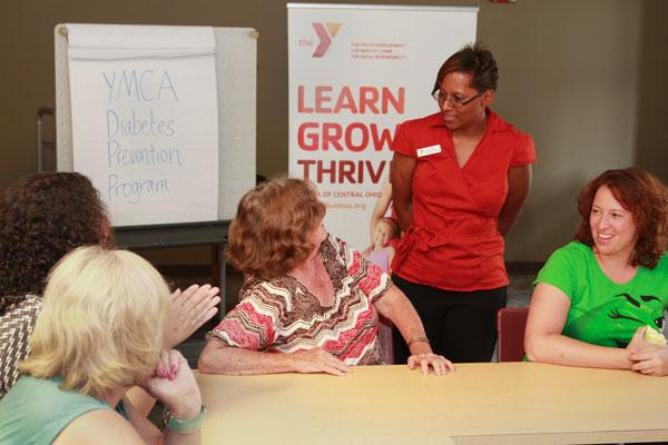 Lori Sparks, standing, leads a diabetes prevention group at the downtown YMCA. It's one of various wellness and prevention programs springing up to gain insurer and government support.