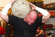 A 170-pound stone made of concrete is lifted in practice.