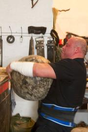 Stanton strains as he lifts a 170-pound stone onto a shelf.