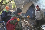 Irwin, left, and Andrews, middle, chat with Jon Peirce, who has been living in a tent.