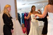 Adrianne Mellen Ramstack, left, has an event planning company that does destination weddings. Here, she helps bride-to-be  Melissa Lonneman check out a gown at La Jeune Mariee in Worthington.