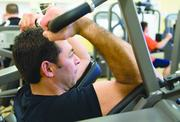 Scotts employee London Rogan works on his biceps in the fitness center.