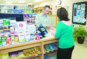 Lanie Fraley, right, picks up a prescription from pharmacist Scott Kijowski at Scotts Miracle-Gro's in-house pharmacy.