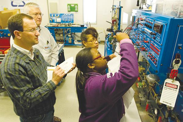 Columbus State now offers training for the biomanufacturing industry. Instructor Larry Miller, background, watches students John Erwin, Dannielle James, in foreground, and Lisa Hartway adjust flow controls for liquids as part of the process of making pharmaceuticals and foods.