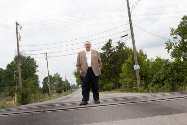 MORPC's Robert Lawler said transporting goods in and out of the Rickenbacker area will be more reliable as a result of the road improvements. He's pictured on Duvall Road at  a railroad crossing. The new connector will provide a route into Rickenbacker that isn't affected by trains.